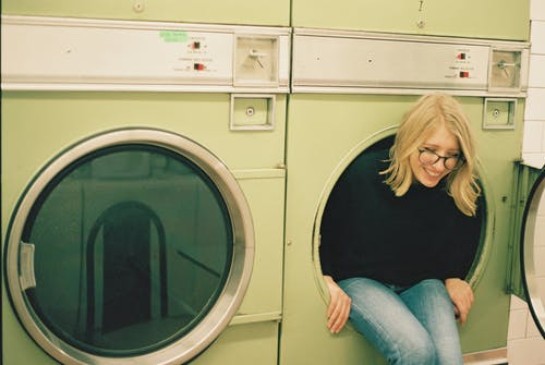 Cheerful woman sitting in laundry machine