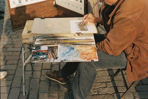 Focused crop artist painting picture on street