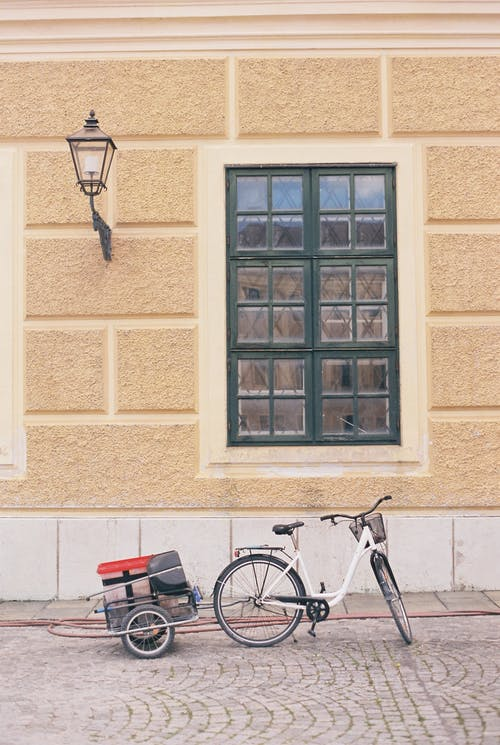 Bicycle with trailer parked on pavement near house facade with window with black frame and lantern on painted brick wall