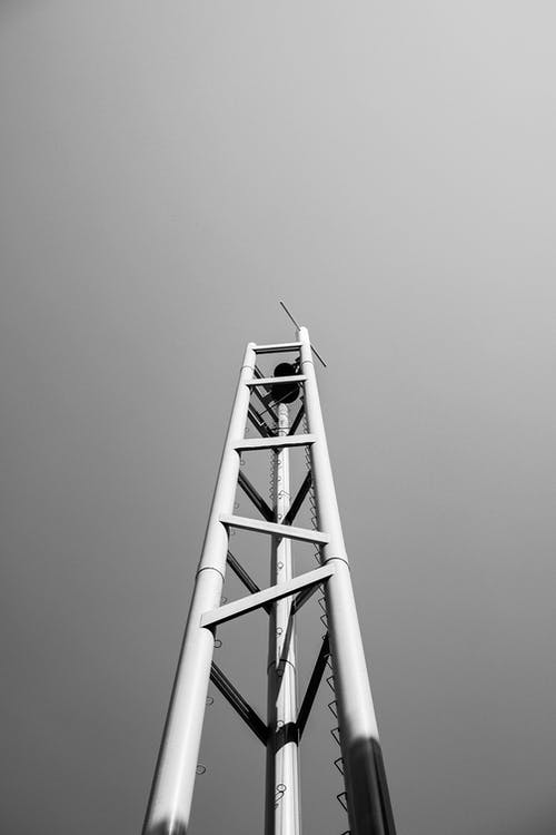 Black and white from below of high metal tower with antenna on top under sky in town