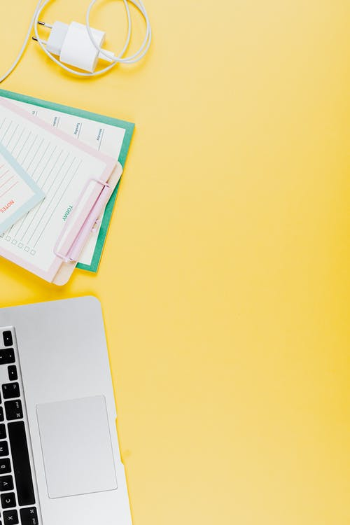 Close-Up Shot of a Laptop beside a Planner on a Yellow Surface