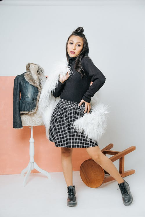 Full body of calm Asian female in skirt with hand on hip and white cape on shoulder looking at camera while standing in studio with white wall with fallen chair and mannequin behind back