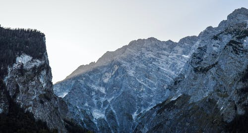 Breathtaking landscape of rough stone mountains with peaks covered on nasty cold day