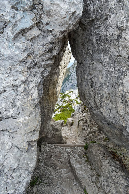 Old rocky cave near green mountains on sunny clear day in wild nature