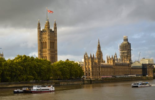 The Westminster Palace on green embankment of the River Thames