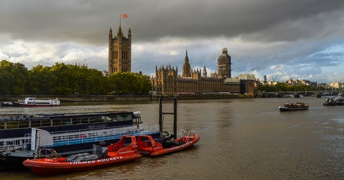 Boats floating on river against Palace of Westminster