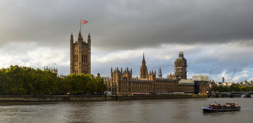 Exterior of Houses of Parliament with flag of England in front of Thames in cloudy day