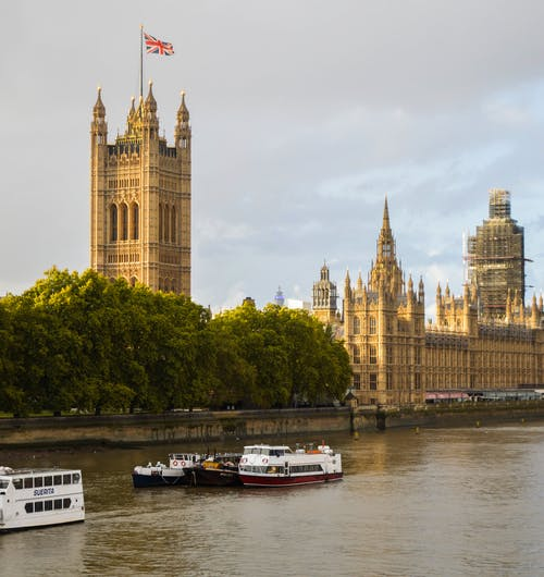 Exterior of Houses of Parliament in front of river in sunlight