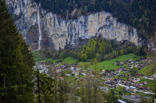 From above of picturesque rocky mountain covered with coniferous trees with waterfall flowing above small village of Lauterbrunnen in Switzerland
