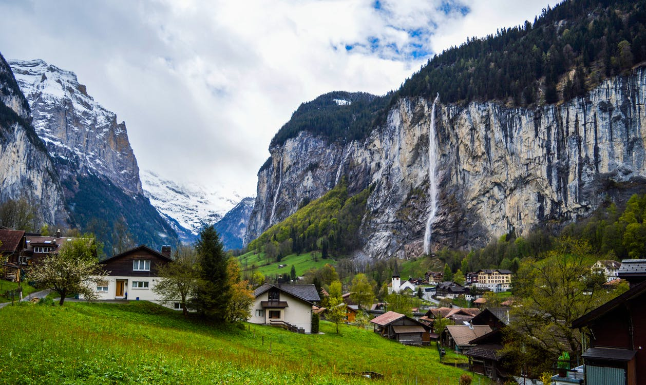 Traditional village houses located on green grassy terrain between huge rocky mountains with snow and trees on peaks in Lauterbrunnen