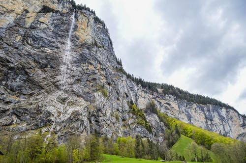 Rocky mountain ridge with flowing waterfall and green vegetation on cloudy day in Switzerland