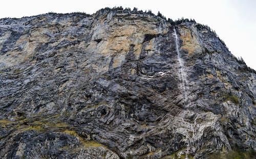 Water cascade streaming through huge rocky ravine