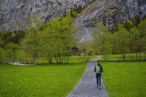 Faceless traveling woman walking on pathway