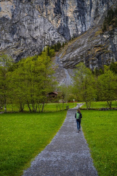 Full body of anonymous distant tourist with backpack strolling on walkway surrounded by grass and trees leading to rocky mountain