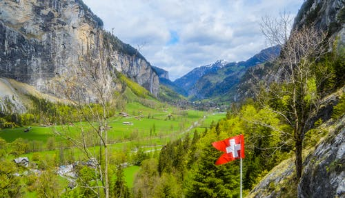 From above of small settlement located on green hill amidst highland with rocky cliff with flag of Switzerland in summer