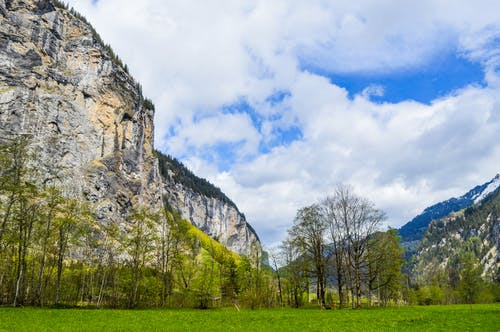 Steep mountain slope in valley with woods