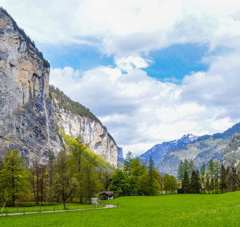 Scenic view of valley with green grass and trees and pathway against rocky mountain cliffs