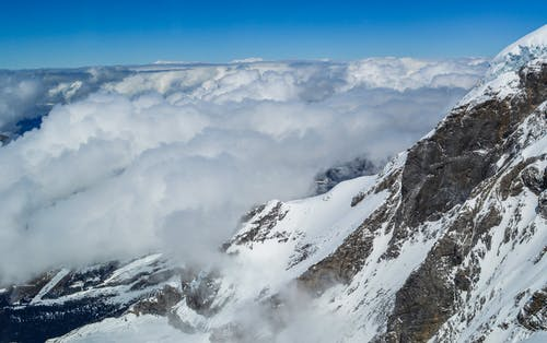 From above spectacular view of mountain rocky slope and fluffy clouds over winter valley