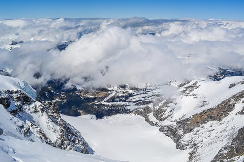 From above amazing steep mountainsides and snowy valley under fluffy clouds against blue sky