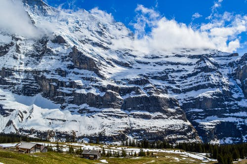 Spectacular alpine landscape of small settlement located on grassy terrain near massive rocky mountain covered with snow in Switzerland