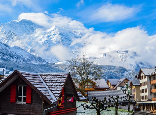 Village with modern cottages placed near high rocky mountains covered with snow in sunny day