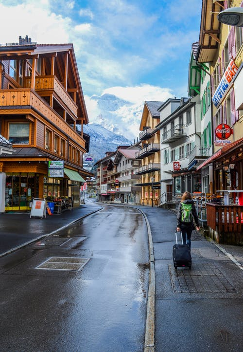 Woman tourist walking on street among colorful buildings against mountains