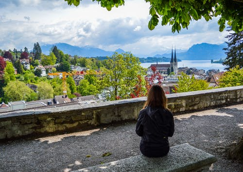 Woman sitting on stone bench and looking at scenery