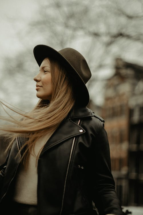 Fashionable woman in hat looking away