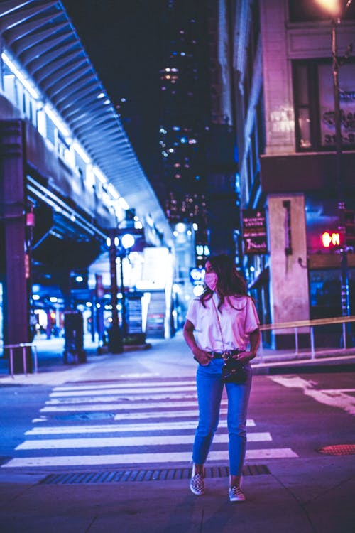 Woman in White Jacket and Blue Denim Jeans Standing on Sidewalk during Night Time