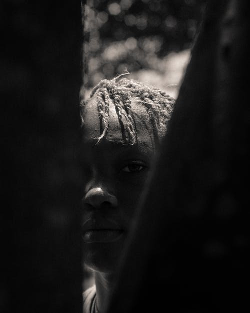 Black and white calm African American teenager with short dreadlocks standing on street and looking at camera through fence planks