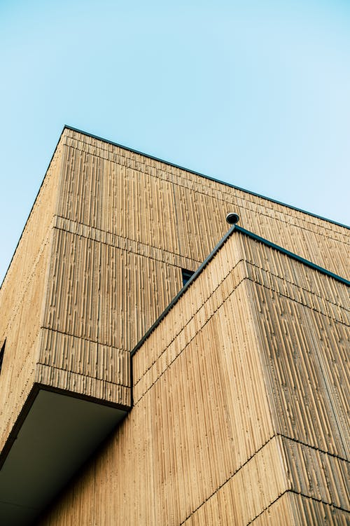 From below of minimalist contemporary building with textured facade against cloudless blue sky