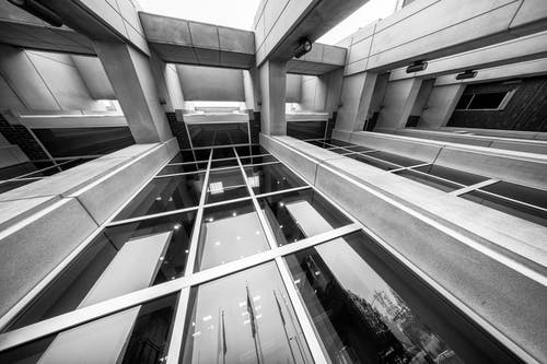 From below of black and white modern building with stone pillars and glass walls reflecting sky