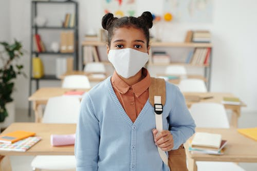 Woman in Blue Long Sleeve Shirt With White Face Mask