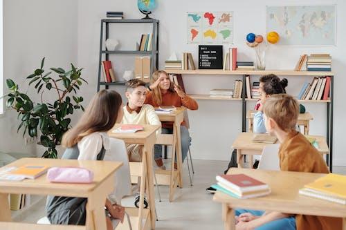 Chica En Camisa De Manga Larga Rosa Sentada En Una Silla De Madera Marrón