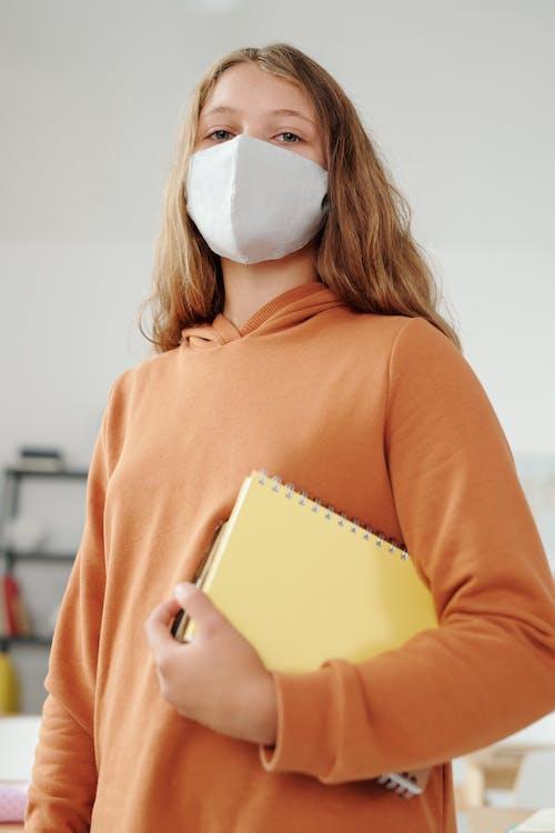 Woman in Orange Long Sleeve Shirt Holding Book