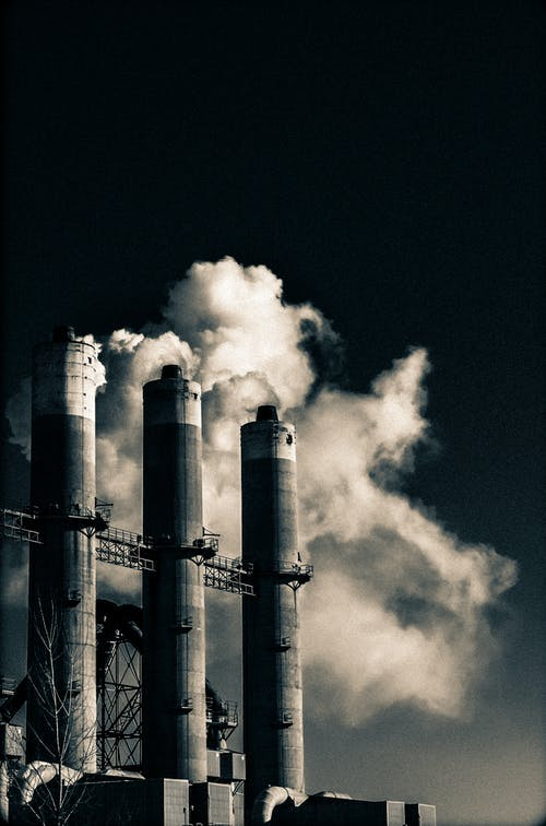 Grayscale Photo of Factory Chimneys