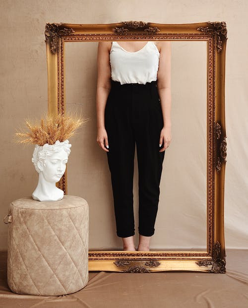 Crop unrecognizable female in stylish apparel behind wooden frame near fabric stool with stone bust and spikes