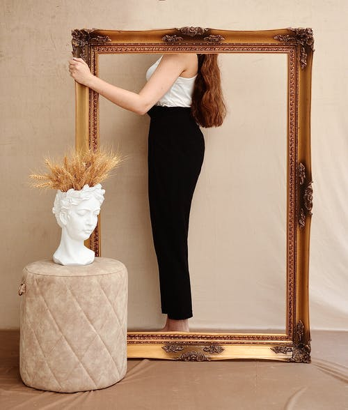 Faceless stylish woman behind ornamental frame in room