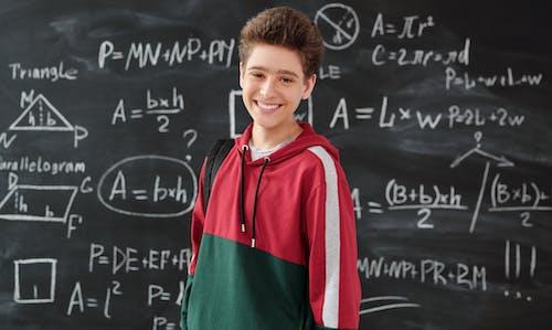Boy in Red Jacket Standing in Front of the Blackboard