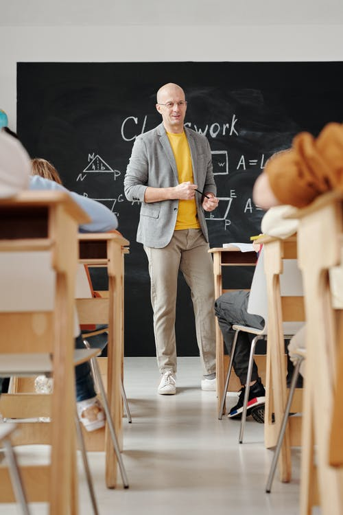 Teacher Standing in Front of a Blackboard