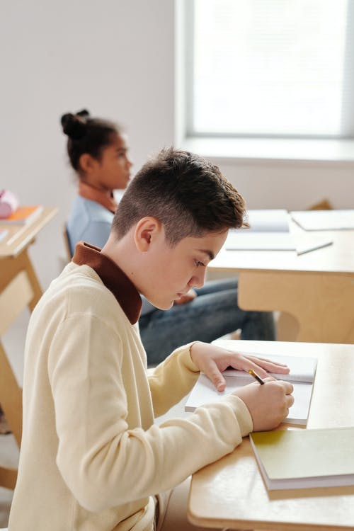 Boy Writing on his Notebook