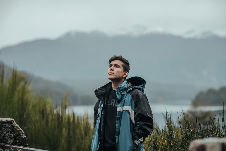 Thoughtful man standing in mountains with lake