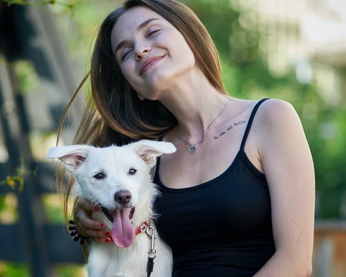 Smiling woman hugging dog in nature