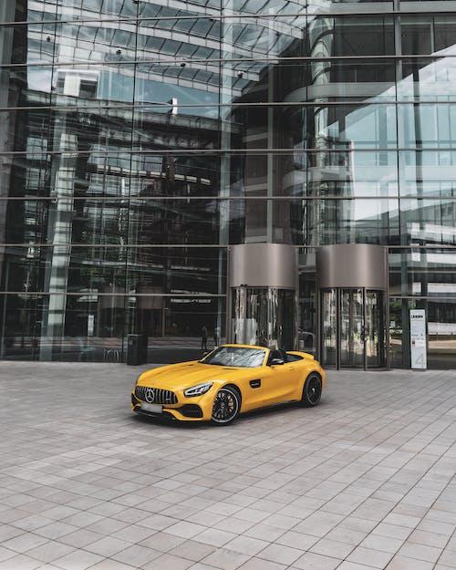 Yellow Porsche 911 Parked Near Glass Walled Building