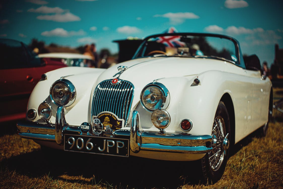 Expensive retro car parked on grass during exhibition