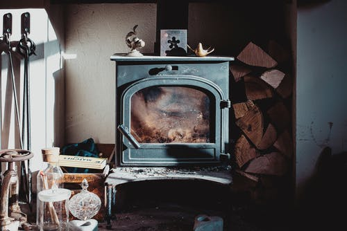 Aged house with retro fireplace and wooden logs