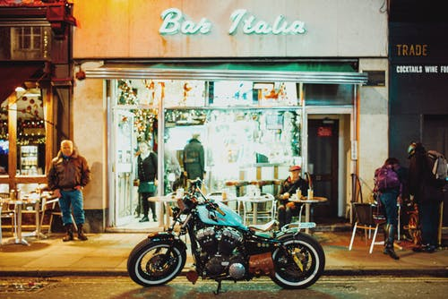 Modern motorbike parked near bar entrance in evening