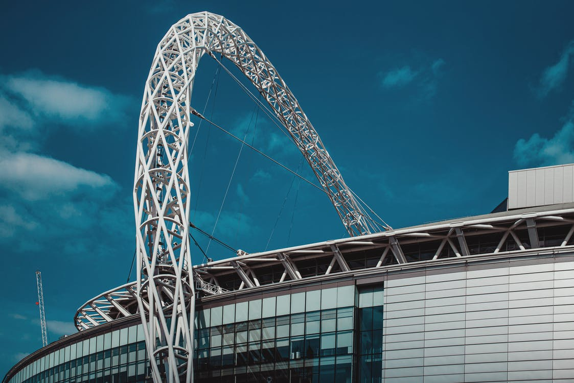 From below of arched roof of modern football stadium with glass walls against blue sky on sunny day in Wembley