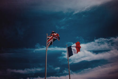Waving flags of France and United Kingdom against blue sky