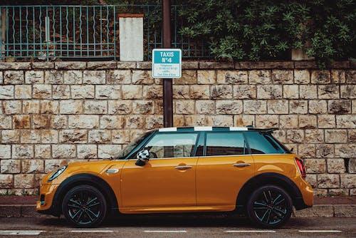 Stylish compact orange car parked near sidewalk in city
